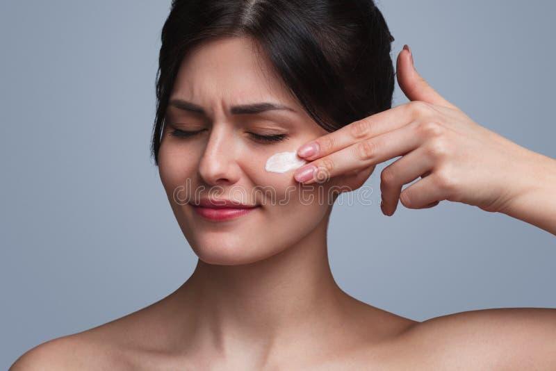 Donna aggrottante le sopracciglia che applica crema fotografia stock