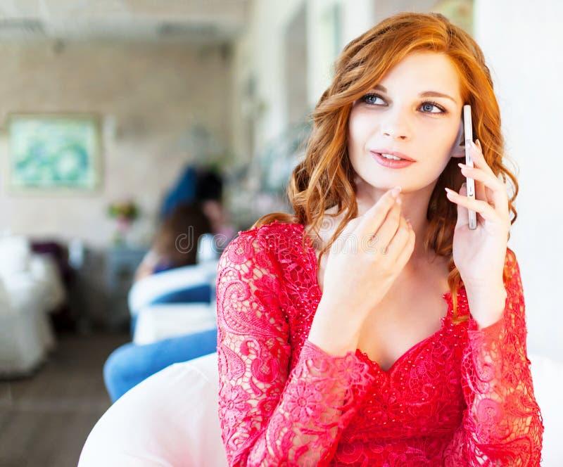 Donna al caffè bevente del caffè e parlare sul telefono cellulare fotografie stock
