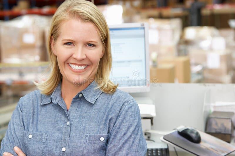 Donna al terminale di calcolatore elettronico nel magazzino di distribuzione