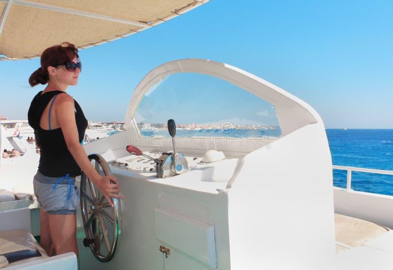 Donna al timone di capitano dell'yacht fotografie stock libere da diritti