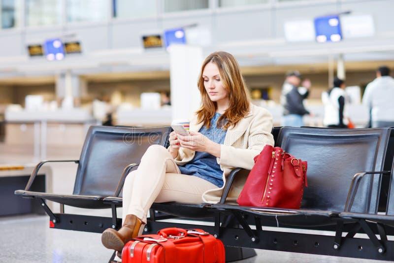 Donna al volo aspettante dell'aeroporto internazionale al terminale immagini stock libere da diritti
