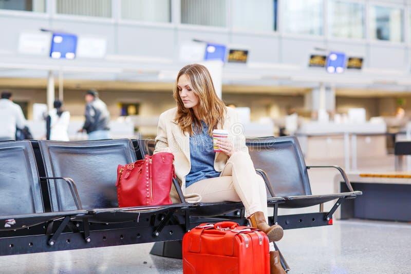 Donna al volo aspettante dell'aeroporto internazionale al terminale fotografia stock