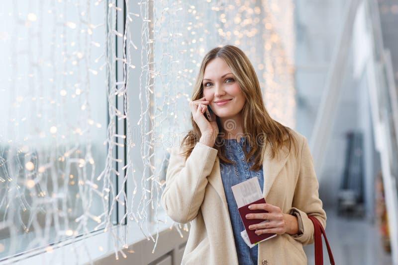 Donna all'aeroporto internazionale che parla tramite telefono cellulare fotografie stock libere da diritti