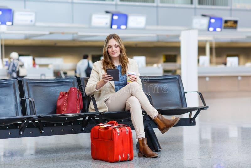 Donna all'aeroporto internazionale, leggente libro elettronico e bevente coffe immagini stock libere da diritti