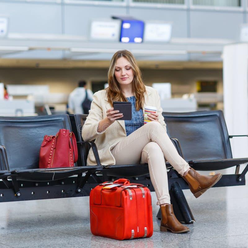 Donna all'aeroporto internazionale, leggente libro elettronico e bevente coffe fotografia stock