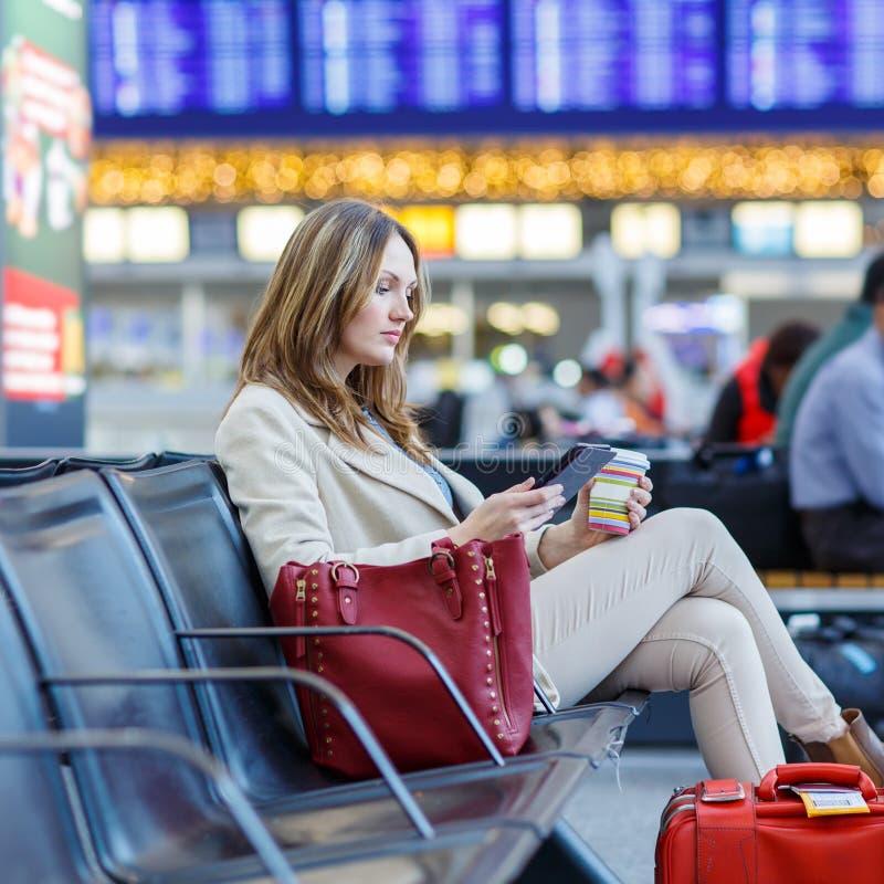 Donna all'aeroporto internazionale, leggente libro elettronico e bevente coffe fotografia stock libera da diritti