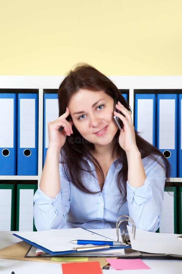 Donna all'ufficio che parla al telefono immagine stock libera da diritti