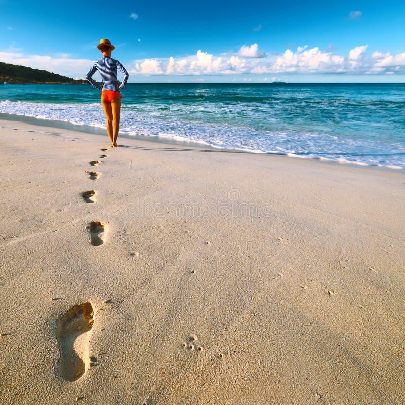 Donna alla bella spiaggia Fuoco sulle orme fotografia stock libera da diritti