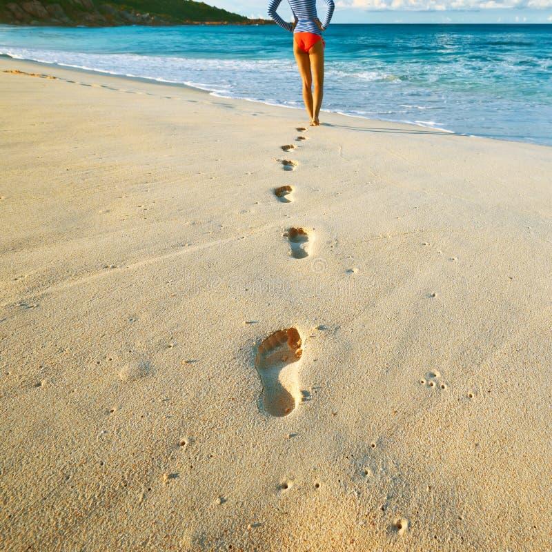 Donna alla bella spiaggia Fuoco sulle orme immagine stock libera da diritti