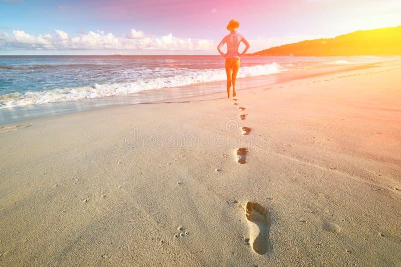 Donna alla bella spiaggia Fuoco sulle orme immagini stock