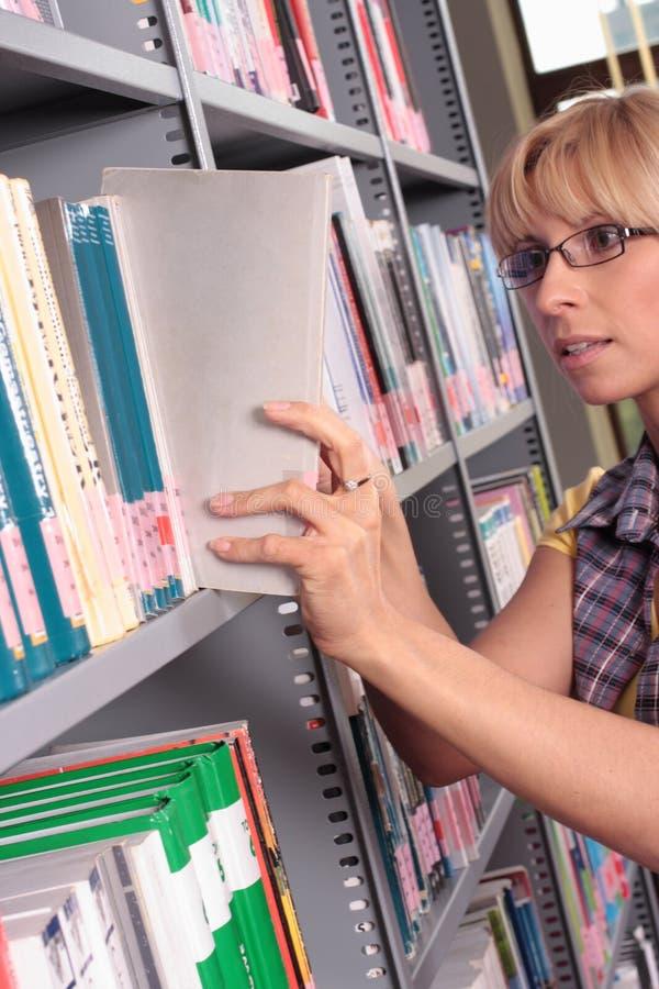 Donna alla mensola delle biblioteche immagine stock libera da diritti