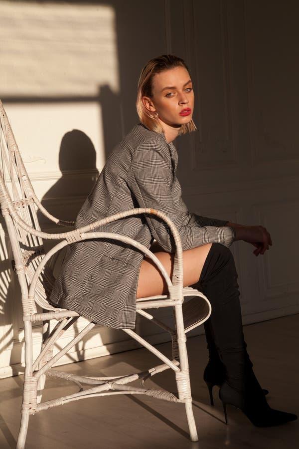 Donna alla moda in biancheria intima che si siede in una poltrona bianca fotografie stock libere da diritti