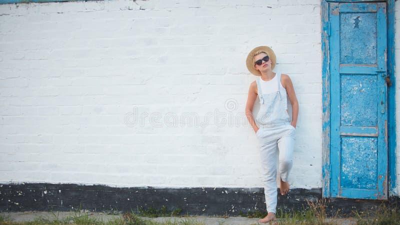 Donna alla moda bionda di abbronzatura abbastanza esile nella posa del cappello e degli occhiali da sole di paglia immagine stock