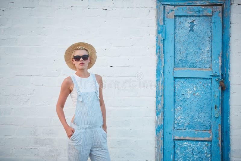 Donna alla moda bionda di abbronzatura abbastanza esile nella posa del cappello e degli occhiali da sole di paglia fotografia stock
