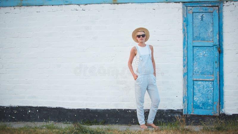 Donna alla moda bionda di abbronzatura abbastanza esile nella posa del cappello e degli occhiali da sole di paglia immagini stock libere da diritti