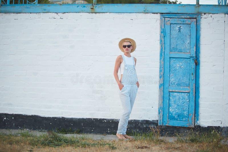 Donna alla moda bionda di abbronzatura abbastanza esile nella posa del cappello e degli occhiali da sole di paglia immagine stock libera da diritti
