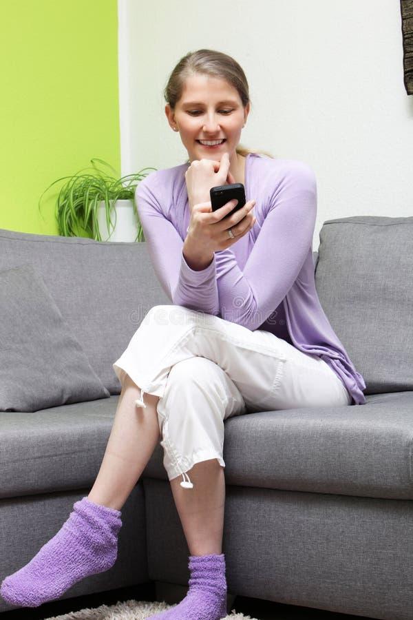 Donna alla moda casuale che legge un messaggio di testo immagini stock libere da diritti