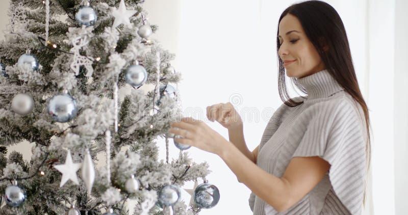 Donna alla moda che ammira un albero di Natale fotografia stock