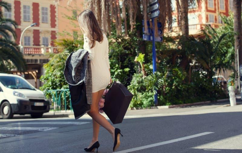Donna alla moda che attraversa la via con il fiore fotografia stock
