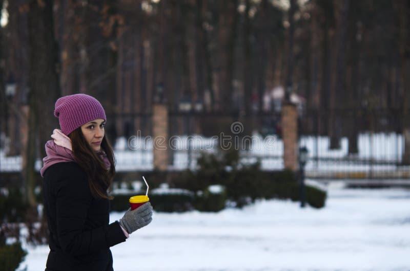 Donna alla moda che beve caffè caldo nel parco di inverno immagine stock libera da diritti