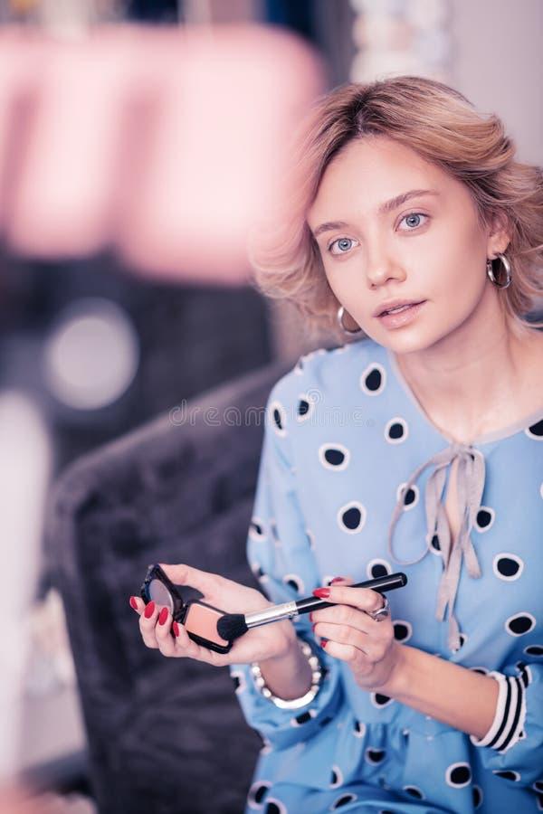 Donna alla moda che esamina macchina fotografica che fa video circa trucco fotografie stock