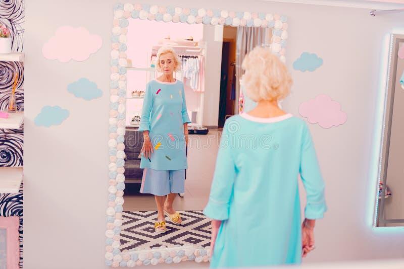Donna alla moda che misura vestito blu lungo vicino allo specchio immagine stock libera da diritti