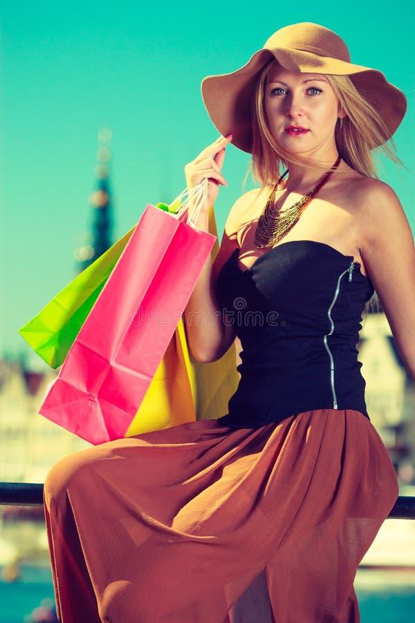 Donna alla moda che riposa dopo la seduta di compera con le borse immagini stock libere da diritti
