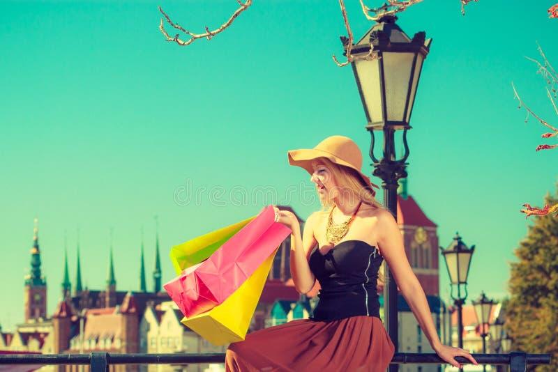 Donna alla moda che riposa dopo la seduta di compera con le borse immagine stock libera da diritti