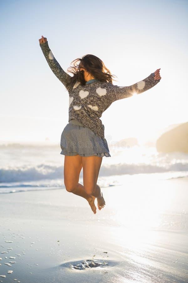 Donna alla moda che salta sulla spiaggia immagini stock
