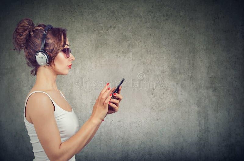 Donna alla moda con il telefono che ascolta la musica fotografia stock