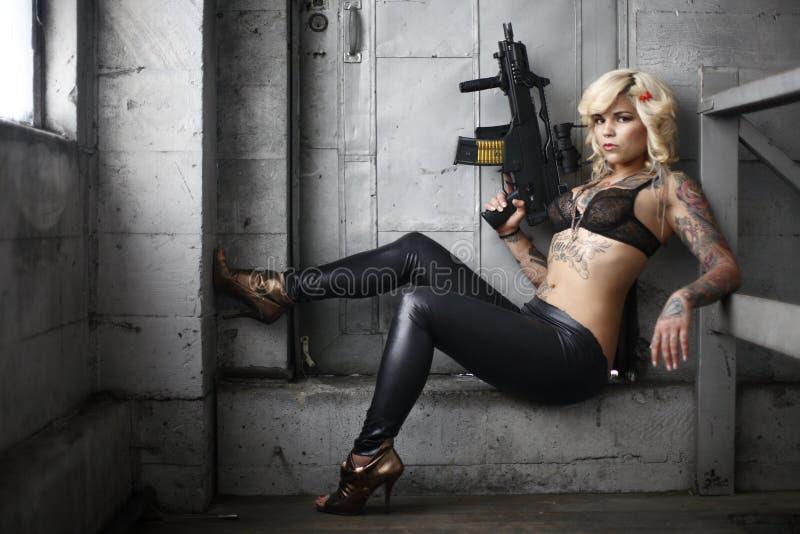 Donna alla moda con la pistola di assalto fotografia stock libera da diritti