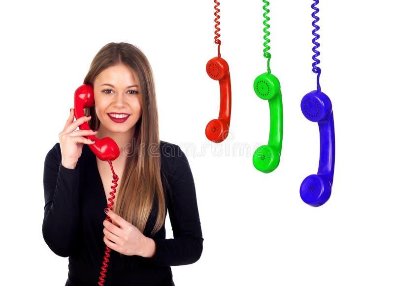 Donna alla moda con un telefono rosso ed altri hangin variopinto dei telefoni fotografia stock