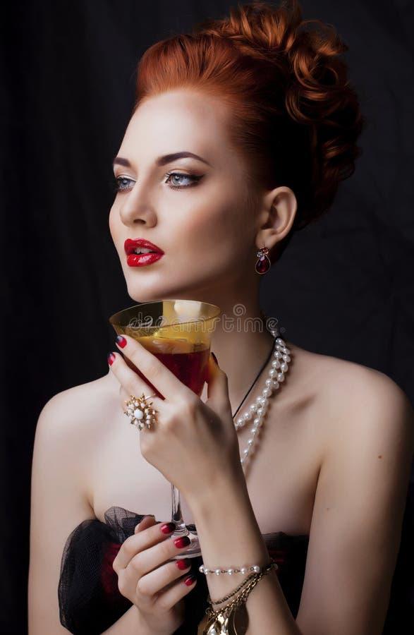 Donna alla moda della testarossa di bellezza con dell'acconciatura del manicure e la fine d'uso della perla dei gioielli su fotografia stock libera da diritti