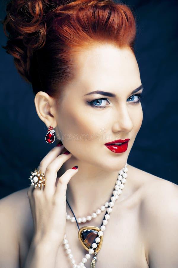 Donna alla moda della testarossa di bellezza con dell'acconciatura del manicure e la fine d'uso della perla dei gioielli su fotografia stock