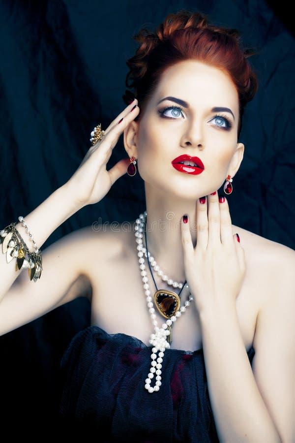 Donna alla moda della testarossa di bellezza con dell'acconciatura del manicure e la fine d'uso della perla dei gioielli su immagine stock libera da diritti