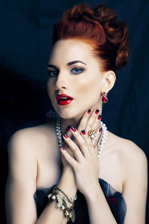 Donna alla moda della testarossa di bellezza con dell'acconciatura del manicure e la fine d'uso della perla dei gioielli su immagine stock