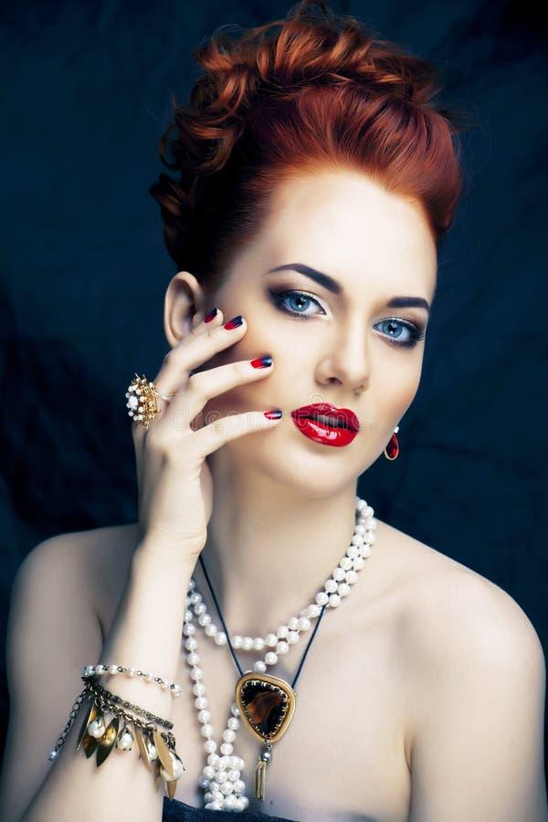 Donna alla moda della testarossa di bellezza con dell'acconciatura del manicure e la fine d'uso della perla dei gioielli su immagini stock libere da diritti