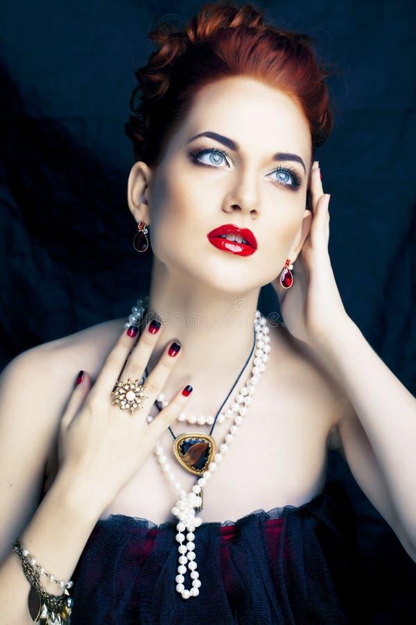 Donna alla moda della testarossa di bellezza con dell'acconciatura del manicure e la fine d'uso della perla dei gioielli su fotografie stock libere da diritti