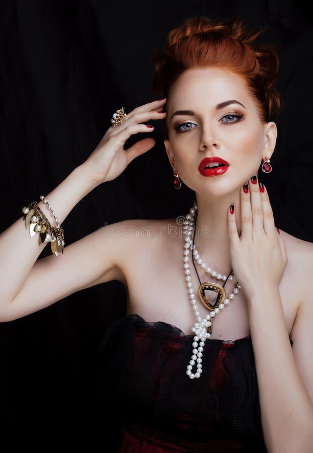 Donna alla moda della testarossa di bellezza con l'acconciatura e fotografia stock