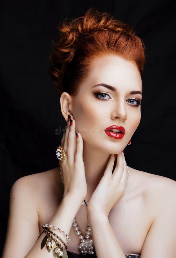 Donna alla moda della testarossa di bellezza con l'uso del manicure e dell'acconciatura immagini stock
