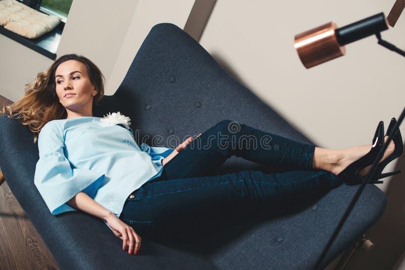 Donna alla moda di affari che prende una rottura Giovane donna attraente che si trova sul sofà grigio in un ufficio moderno Ragaz fotografie stock