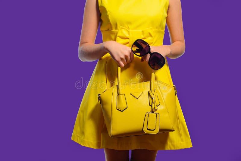 Donna alla moda elegante in vestito giallo con la borsa e gli occhiali da sole fotografia stock