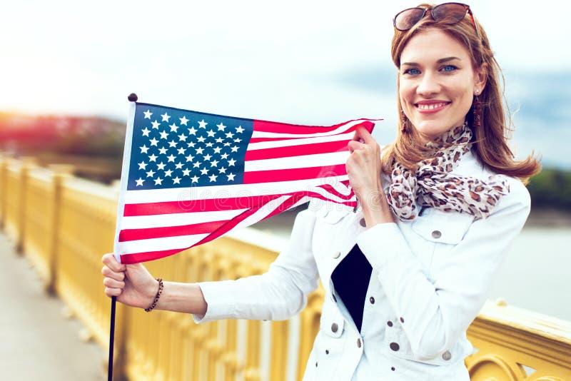 Donna alla moda giovane del patriota con il sorriso a trentadue denti che allunga la bandiera di U.S.A. nel tramonto fotografie stock