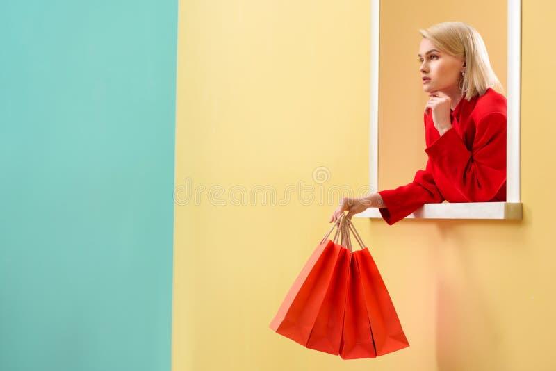 donna alla moda pensierosa in abbigliamento rosso con i sacchetti della spesa rossi che guardano fuori fotografia stock libera da diritti