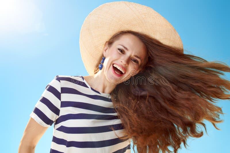 Donna alla moda sorridente con capelli d'ondeggiamento contro cielo blu fotografie stock libere da diritti
