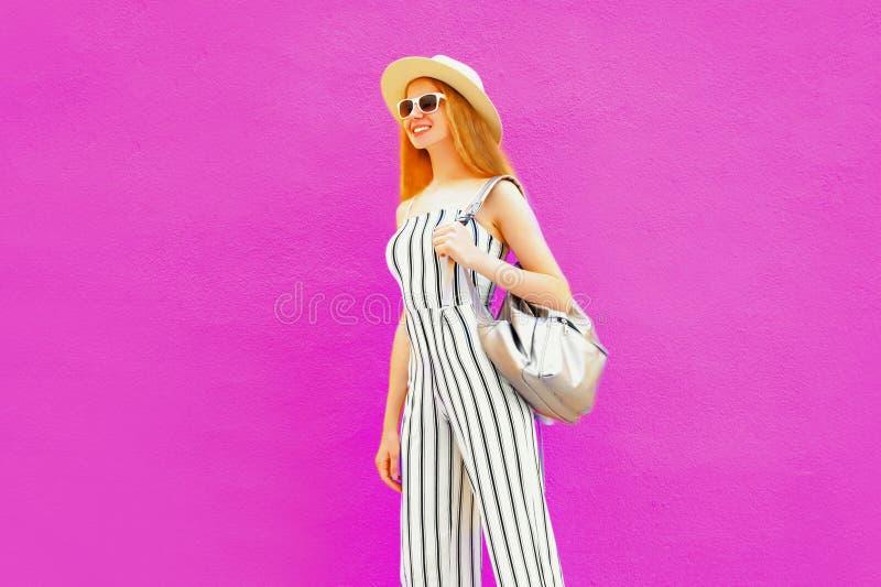 Donna alla moda sorridente felice che cammina in cappello di paglia del giro di estate, tuta a strisce bianca sulla parete rosa v fotografia stock