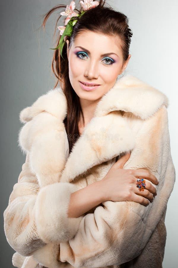 Donna alla moda in un cappotto di pelliccia immagine stock