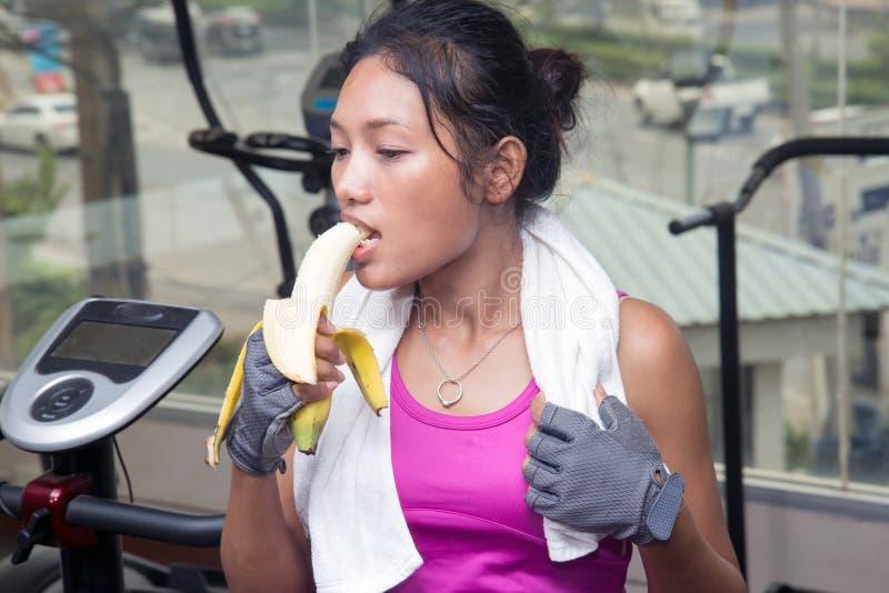 Donna alla palestra che mangia una banana immagine stock