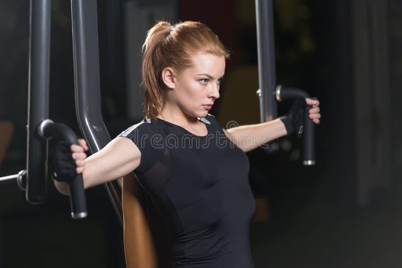 Donna alla palestra di sport che fa gli esercizi di armi su una macchina immagini stock