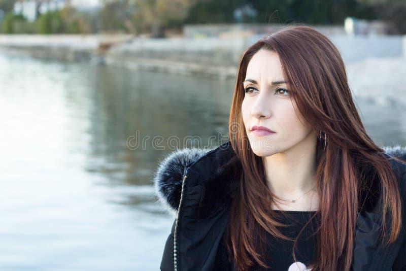 Donna alla spiaggia nell'inverno che distoglie lo sguardo, pensante fotografia stock libera da diritti